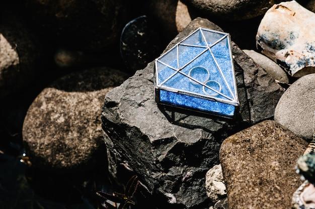 Les bagues de fiançailles de mariage en argent doré se trouvent dans une boîte en métal en forme de verre en forme de diamant.