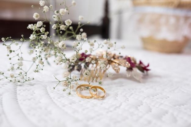 Bagues de fiançailles pour un mariage avec petites fleurs derrière