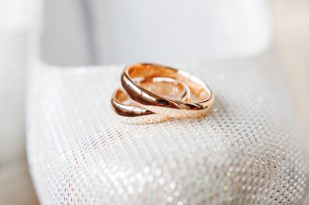Bagues de mariage dorées sur des chaussures de mariée avec des strass. détails de bijoux de mariage. symbole de l'amour et du mariage.