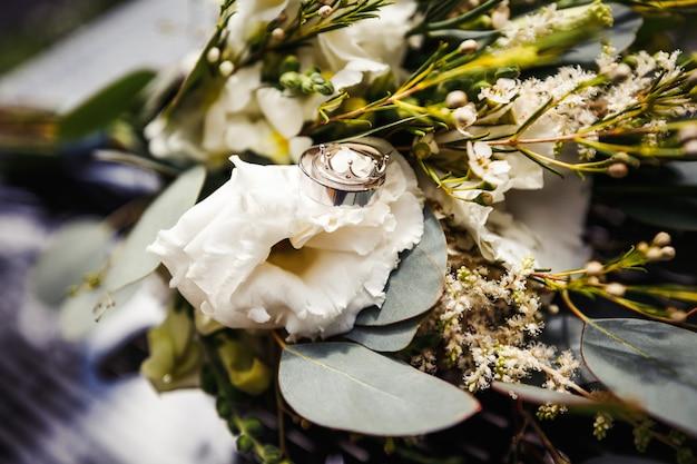 Bagues de mariage dorées élégantes sur les fleurs