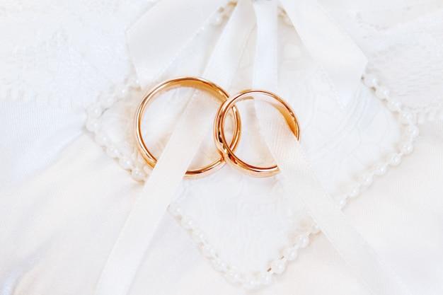 Bagues de mariage dorées sur fond de soie blanche. détails de mariage. symbole de l'amour et du mariage.
