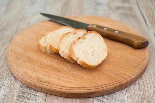 Baguette avec un couteau et une planche à découper sur une vieille table en bois.