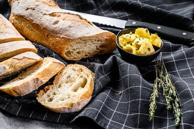 Baguette française au beurre pour le petit déjeuner. fond noir. vue de dessus