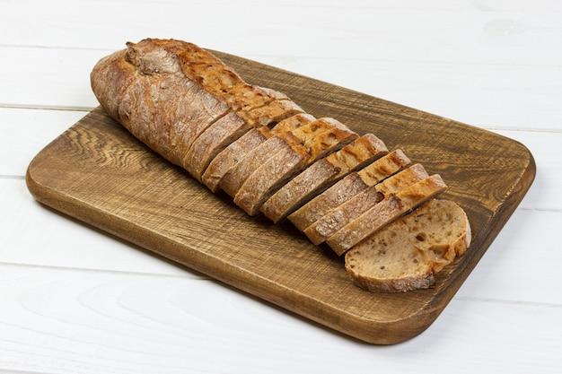Baguette française sur une planche à découper sur une table rustique blanche