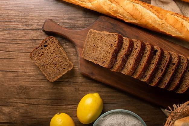 Baguette française avec des tranches de pain brun et des citrons