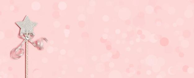 Baguette magique, étoile argentée brillante avec éclat sur rose tendre