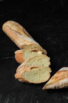 Baguette de pain frais tranchés français isolé sur fond noir close up