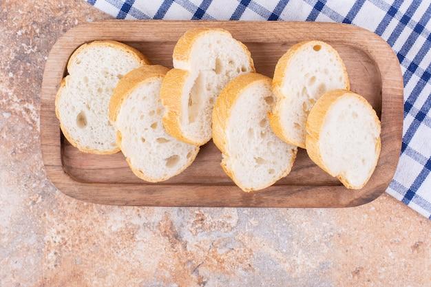 Baguette en tranches sur une assiette en bois sur un torchon, sur le marbre.