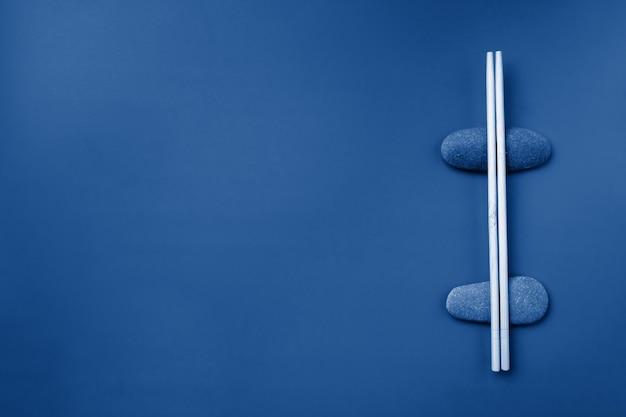 Baguettes en bois clair reposent sur des pierres ovales sur fond bleu