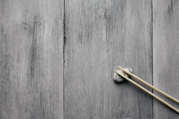Baguettes en bois pour la cuisine asiatique chinoise sur fond de bois clair et pierre