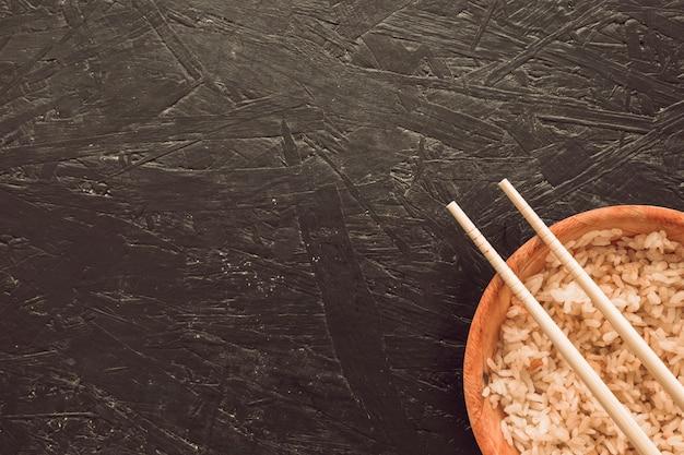 Baguettes sur le bol de riz cuit dans un coin de fond rugueux