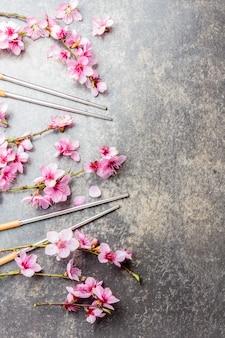 Baguettes et branches de sakura sur pierre grise