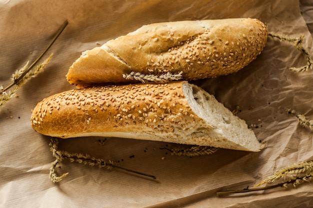 Des baguettes françaises aux graines de sésame sur un sac en papier reposent sur une table en bois.