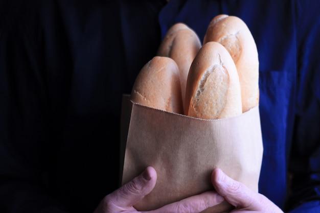Baguettes françaises dans un sac en papier entre des mains masculines