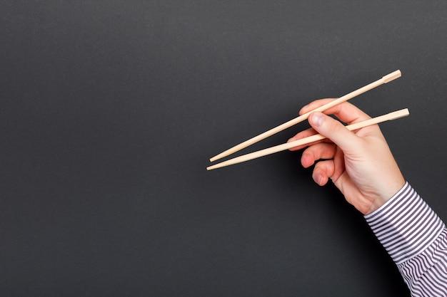 Baguettes à main mâle sur fond noir. cuisine asiatique traditionnelle