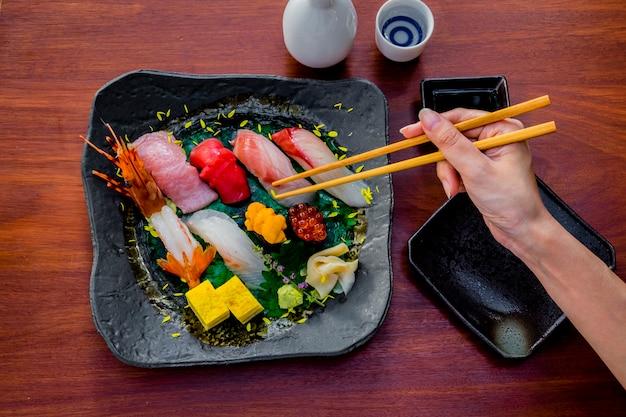 Baguettes à la main poisson cru sushi set cuisine japonaise