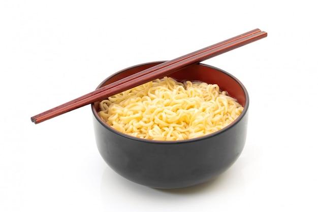 Baguettes de nouilles dans un bol noir sur fond blanc