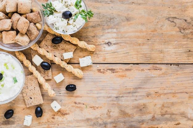 Baguettes, olives, pain croquant et pâtisseries avec un bol de fromage sur une table en bois