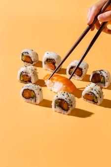 Des baguettes ramassant des sushis au nigiri dans des rouleaux de maki