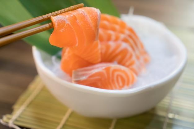 Baguettes avec sashimi de saumon avec sashimi de saumon sur glace dans un bol.
