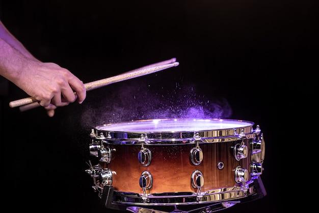 Baguettes de tambour frappant la caisse claire avec des éclaboussures d'eau sur un espace noir sous l'éclairage de studio se bouchent.