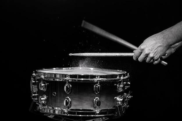 Baguettes de tambour frappant la caisse claire avec des éclaboussures d'eau sur fond noir sous l'éclairage de studio. noir et blanc. photo en mouvement.