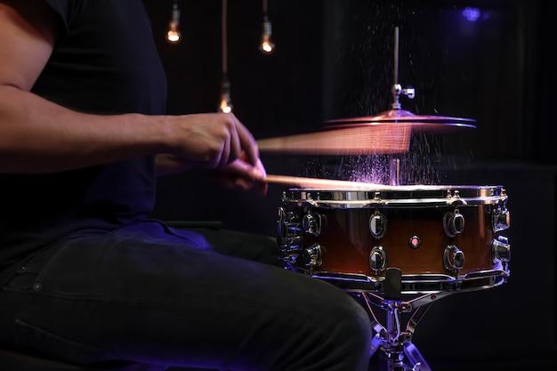 Baguettes de tambour frappant la caisse claire avec des éclaboussures d'eau sur fond noir sous l'éclairage de studio se bouchent.