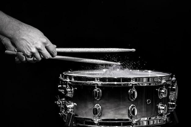 Baguettes de tambour frappant la caisse claire avec des éclaboussures d'eau sur fond noir sous l'éclairage de studio.