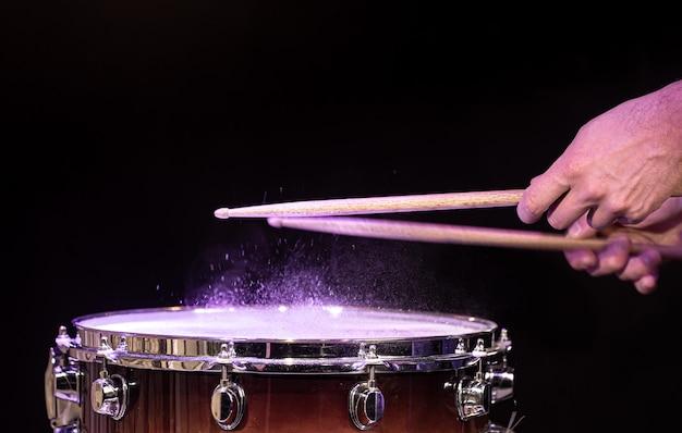 Baguettes de tambour frappant la caisse claire avec des éclaboussures d'eau sur fond noir sous l'espace de copie d'éclairage de studio.
