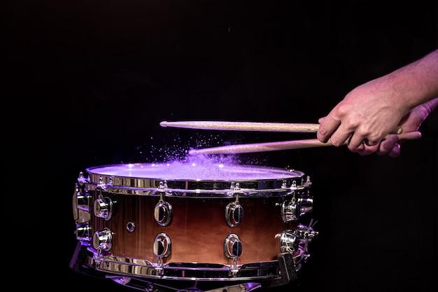 Baguettes de tambour frappant la caisse claire avec des éclaboussures d'eau sous l'éclairage du studio.