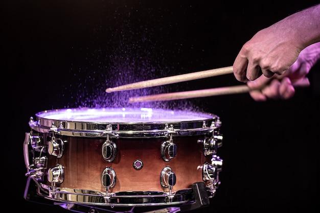 Baguettes de tambour frappant la caisse claire avec des éclaboussures d'eau sous l'éclairage de studio se bouchent.