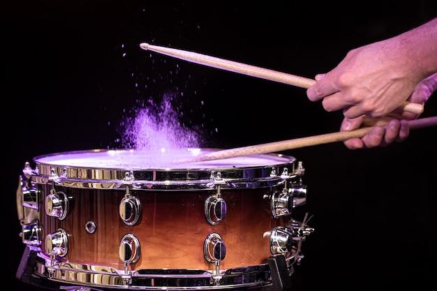 Baguettes de tambour frappant la caisse claire avec des éclaboussures d'eau