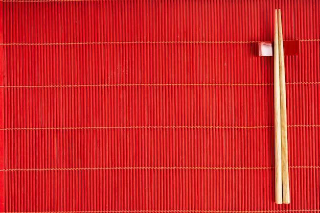 Baguettes sur le tapis de bambou rouge sur le fond de pierre grise avec copie espace. maquette pour le menu.