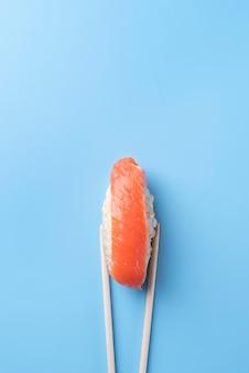 Baguettes tenant la vue de dessus de sushi