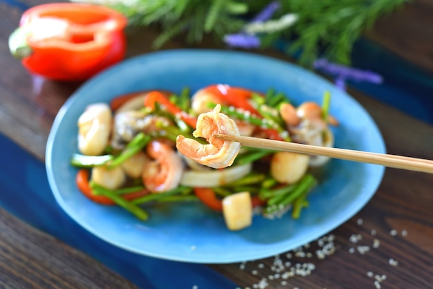 Les baguettes tiennent les crevettes contre la nourriture asiatique