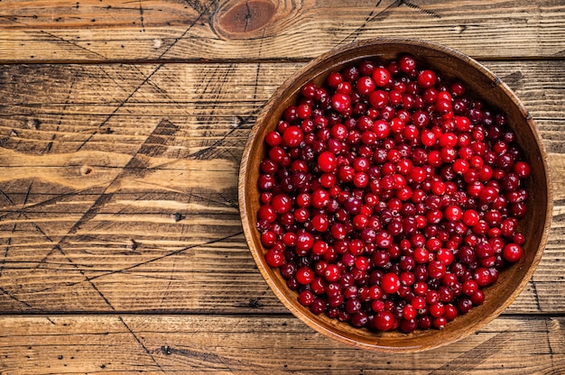 Baie de canneberge rouge dans une assiette en bois