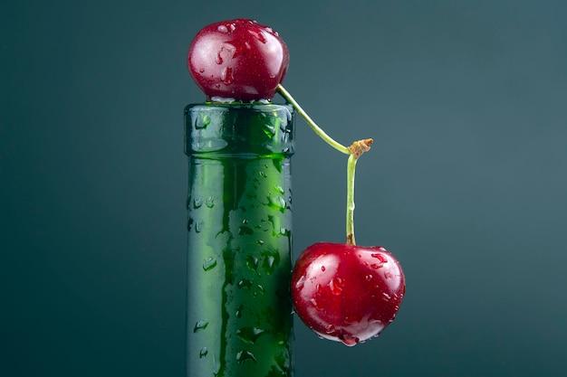 Baie de cerise fraîche avec des gouttelettes d'eau sur une bouteille verte. nourriture saine pour le petit déjeuner. fruits de la végétation. dessert aux fruits