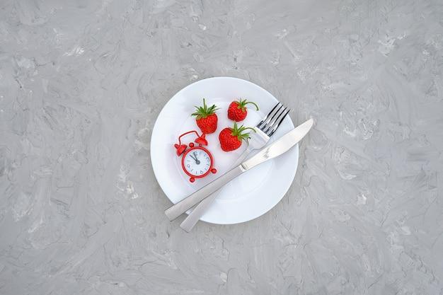 Baie de fraises mûres rouges sur une assiette blanche, des couverts et un réveil rouge sur une table en pierre grise
