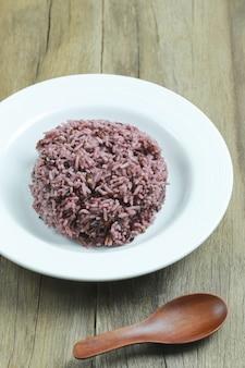 Baie de riz biologique dans un plat blanc.