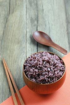 Baie de riz biologique dans un plat en bois sur fond de bois.