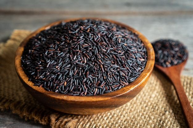 Baie de riz dans un bol en bois avec cuillère sur table en bois