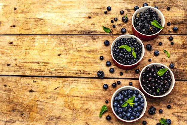 Baies assorties de couleurs bleues et noires: myrtille, myrtille, groseille et mûre. vieux fond de table en bois, vue du dessus