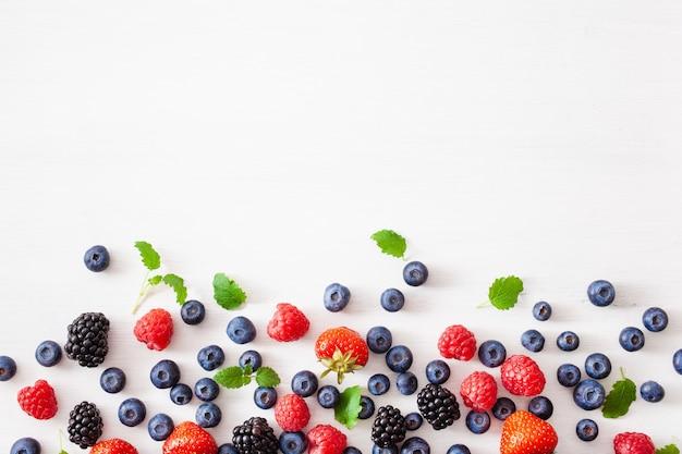 Baies assorties sur fond blanc. myrtille, fraise, framboise, mûre