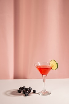 Baies bleues fraîches avec un cocktail sur un bureau blanc