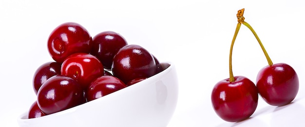 Baies de cerise dans une tasse blanche sur fond blanc cerises mûres isolées cerise délicieuse rouge