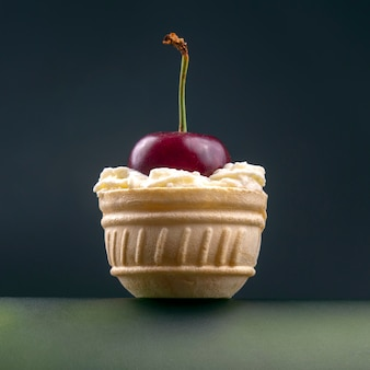 Les baies de cerises fraîches dans la crème de lait se trouvent dans un panier à gaufres. nourriture saine pour le petit déjeuner. fruits de la végétation. dessert aux fruits