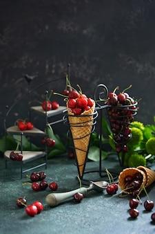 Baies de cerises fraîches juteuses dans un cône de gaufre sur un stand vintage.