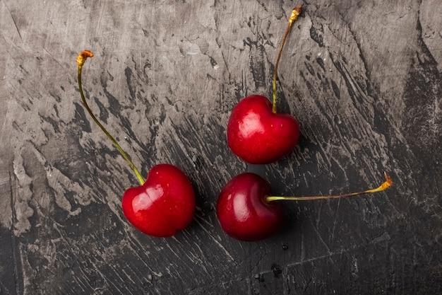 Baies de cerises fraîches sur une table sombre