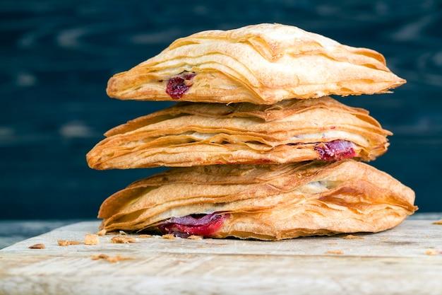 Baies de cerises rouges mûres comme garniture pour les petits pains à la farine, les pâtisseries sucrées et fraîches avec une croûte croustillante et une garniture sucrée
