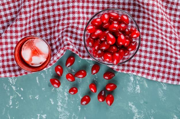Baies de cornel dans un bol avec boisson sur plâtre et tissu de pique-nique